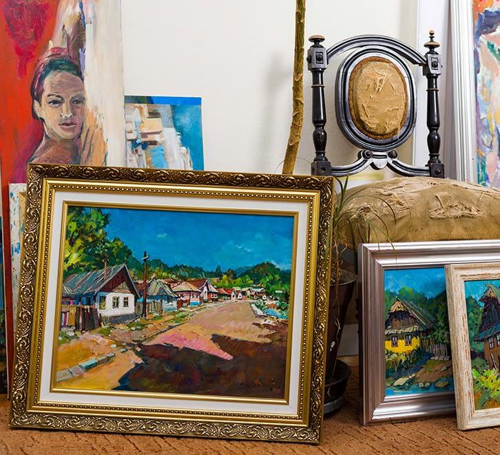 Multiple framed art pieces sitting on the floor